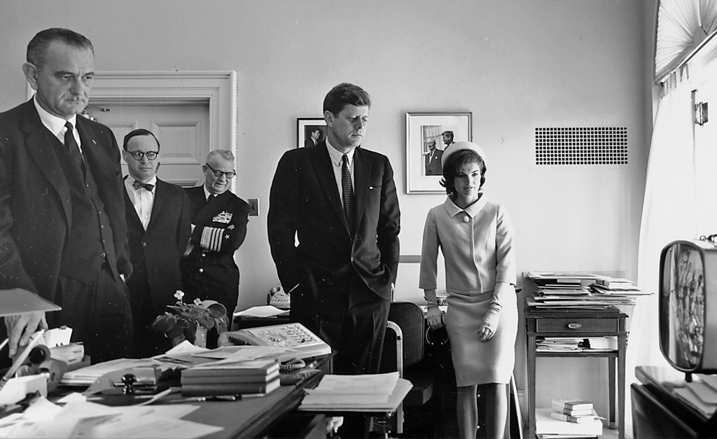 Photograph of JFK and others watching a television screen