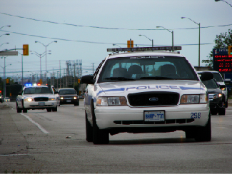 A photograph shows two police cars driving, one with its lights flashing.