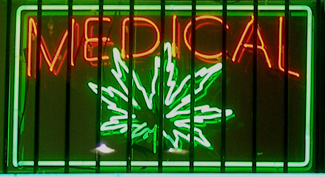 "A photograph shows a window with a neon sign. The sign includes the word ""medical"" above the shape of a marijuana leaf."