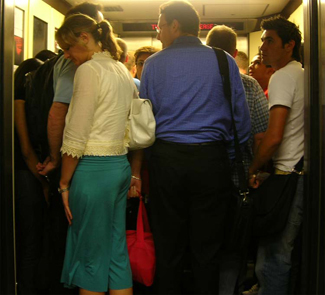 A crowded elevator is shown. There are many people standing close to one another.