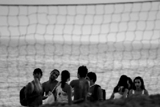 Several people are congregated by the beach. There is a net in the background.