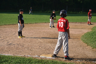 A photograph of children playing baseball is shown. Five children are in the picture, two on one team, and three on the other.