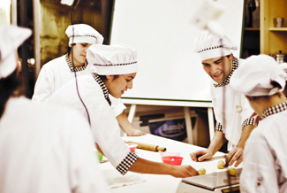 A photograph shows several chefs preparing food together in a kitchen.