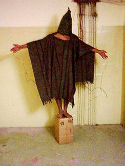 A photograph shows a person standing on a box with arms held out. The person is covered in shawl-like attire and a full hood that covers the face completely.