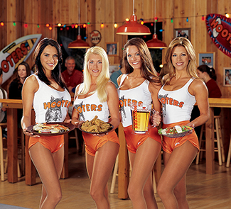 """Four Hooters employees are pictured standing side by side. Three of them are holding plates of food and the other is holding a pitcher of beer. Each of them is wearing a white tank top that says """"Hooters,"""" and high cut shorts."""