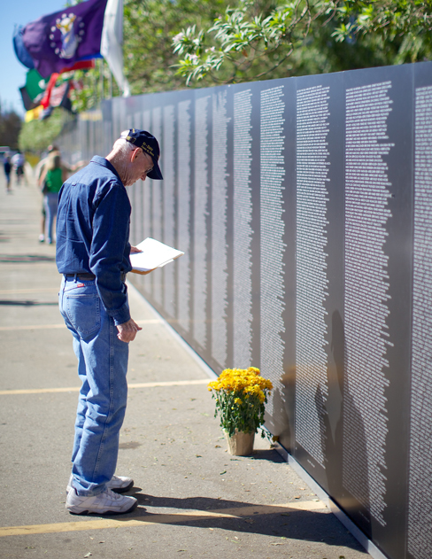 A photograph shows a person looking at the Vietnam Traveling Memorial Wall.